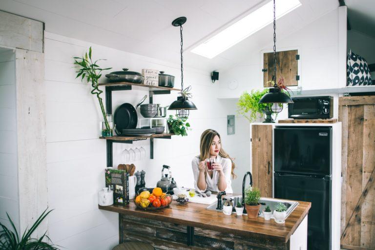 בחורה יושבת על אי במטבח מעץ